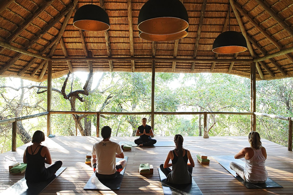 People doing yoga on the The Londolozi Yoga Deck