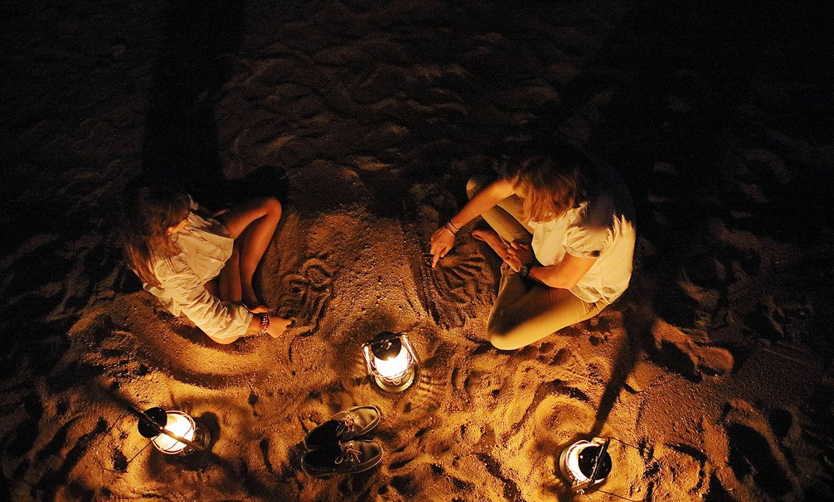 Children kids sitting around a fire at night while on safari at Londolozi